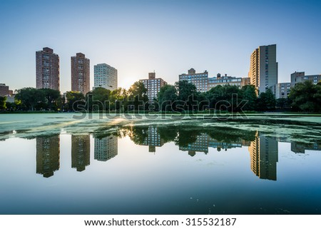 Sunrise over buildings and the Harlem Meer, in Manhattan, New York.