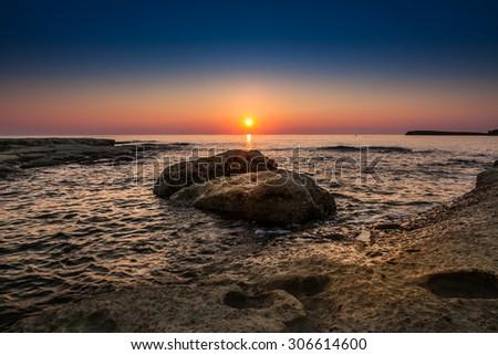 Sunrise over calm Mediterranean waters in Malta - stock photo