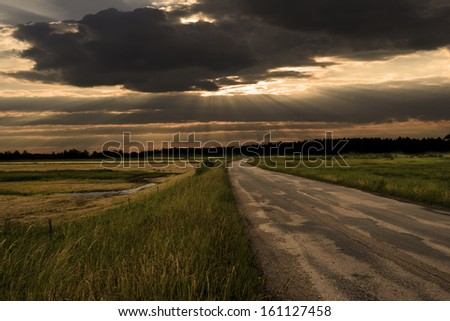 Sunrise over country road - stock photo