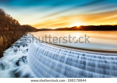 Sunrise over Croton Dam, NY and its stepped spillway waterfall. A very long exposure and the natural motion blur creates an artistic smooth and silky effect on the falling water. - stock photo