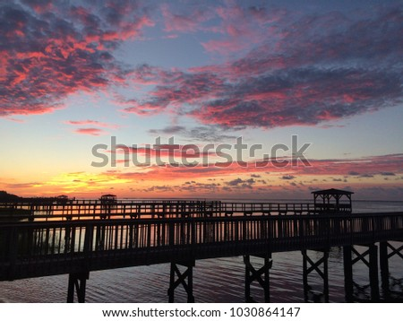 Sunrise over docks along river.