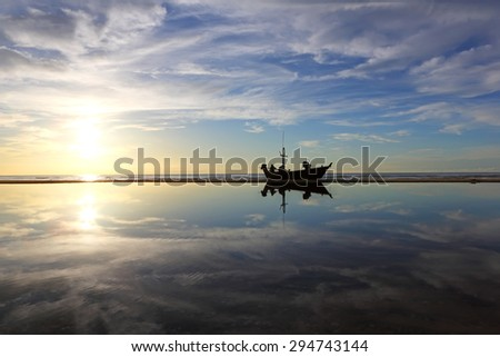 Sunrise over fishing boat with water reflection at Cha-am Beach,Petchburi of Thailand