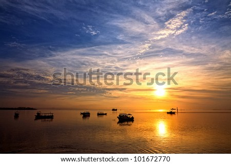 sunrise over fishing boats on Bali - stock photo