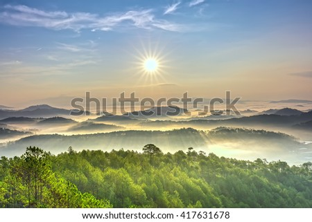 Sunrise over hill with the sun radiating golden rays pierced the hills with pine trees covered with morning dew beautiful ray beam forming to welcome the new day so simple in Da lat, Vietnam - stock photo
