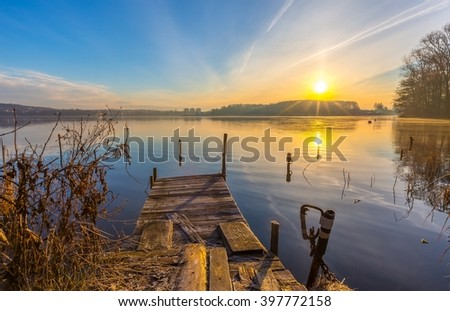 Sunrise over lake at end of winter. Frosty morning with sunrise over lake. - stock photo