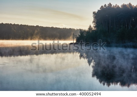 Sunrise over lake. Silhouettes of forest trees and fog over the lake