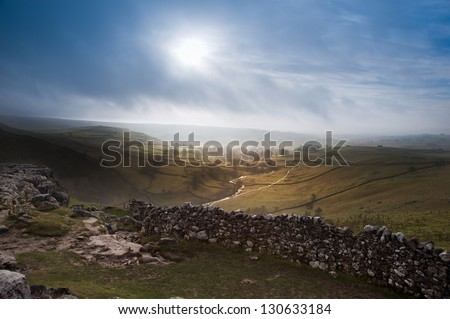 Sunrise over Malham Cove and Dale in Yorkshire Dales National Park with sunlight bursting through mist - stock photo