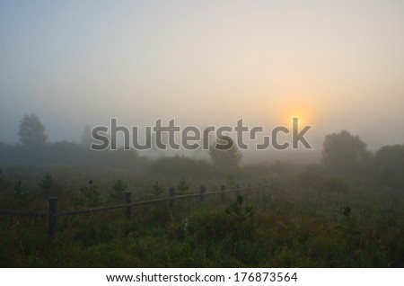 Sunrise over misty grassland with wooden fence in the foreground. - stock photo