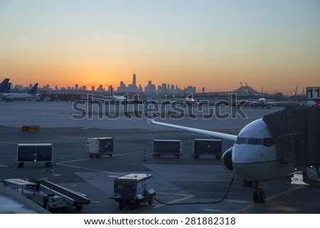 Sunrise over New York City with busy airport in the foreground. - stock photo