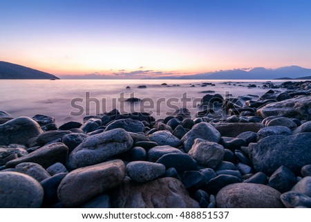 Sunrise over sea and rocks. Photo was taken with long exposure to blur water at Crete, Greece