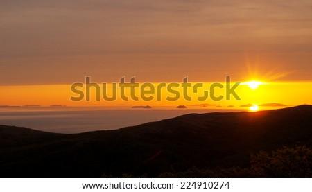 Sunrise over sea, orange sky - stock photo