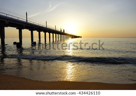 Sunrise over sea with silhouette fishing pier on foreground,Close up,select focus with shallow depth of field:ideal use for background.