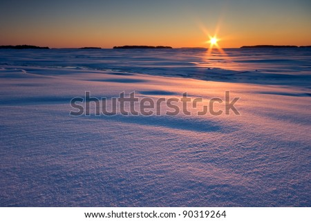 Sunrise over snow covered beach and sea