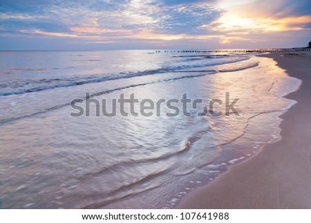Sunrise over the Baltic sea, Poland. Landscape photograph of polish shoreline photographed at sunrise. Beautiful colorful summer scene full of warm colors. - stock photo