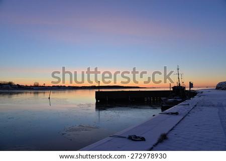 sunrise over the harbor in winter - stock photo