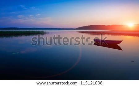 Sunrise over the lake. The first rays of sun. - stock photo