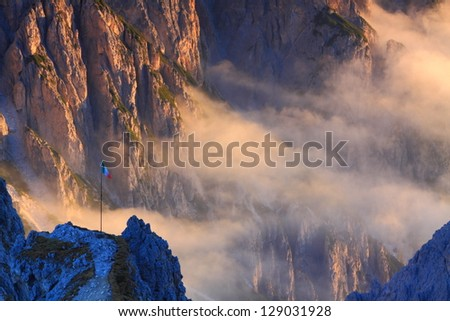 Sunrise over the mountains, clouds and Italian flag, Dolomite Alps, Italy - stock photo