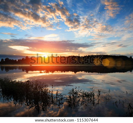 Sunrise over the river. The first rays of sun. - stock photo