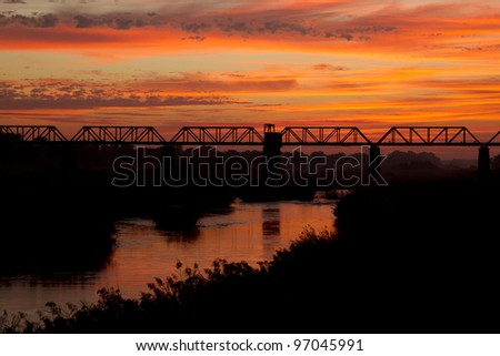 Sunrise over the Sabi River, Kruger National Park, South Africa. The railway bridge at Skukuza Camp - stock photo