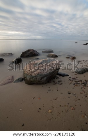 Sunrise over the sea. Beautiful long exposure landscape of rocky shore. Vintage landscape.