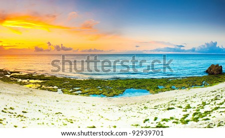 Sunrise over the sea. Stone on the foreground. Panorama - stock photo