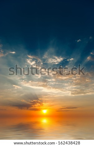Sunrise over the sea with the sun's rays - stock photo