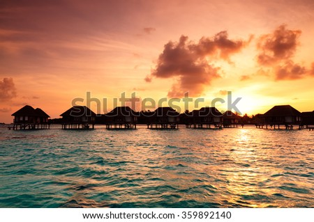 Sunrise over water bungalows on a cloudy day at the end of rainy season in Maldives. - stock photo