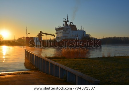 Sunrise overlooking a boat launch ramp on the Cheboygan Michigan river with the US Coast Guard Cutter Mackinaw