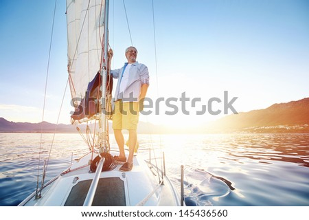 sunrise sailing man on boat in ocean with flare and sunlight on calm morning on the water - stock photo