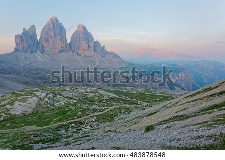 Sunrise scenery of Dolomiti with vertical peaks of Drei Zinnen (Tre Cime di Lavaredo) bathed in golden sunlight & distant mountains lit up by alpenglow under dramatic dawning sky in South Tyrol, Italy