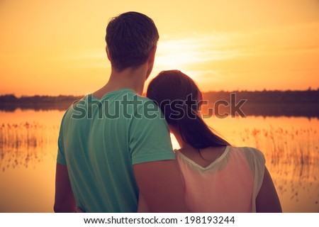 sunrise sea coast couple carefree embracing - stock photo