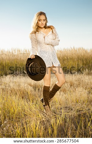 Sunrise shot of a pretty young model on meadow - stock photo
