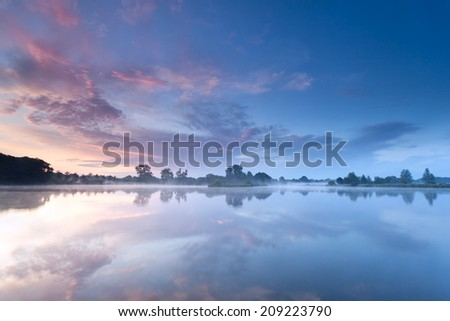 sunrise sky reflected in river during misty morning - stock photo