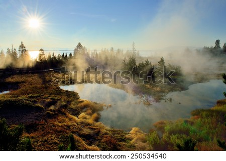 sunrise, steaming geysers and a lake in West Thumb area in Yellowstone National Park, Wyoming - stock photo