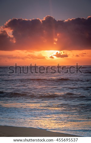 Sunrise/sunset above the ocean with bright vibrant clouds and sky