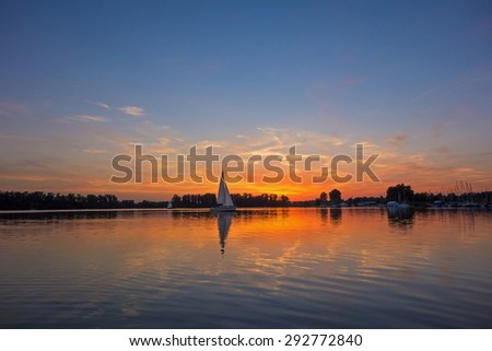 sunrise / sunset at a lake with sailing boats - stock photo