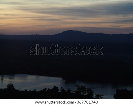 sunrise sunset twilight time colour scene tropical hills trees mountain view silhouette with small lake surrounding with green tropical natural environment in dark shadow under smooth cloudy sky - stock photo