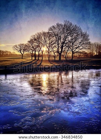 Sunrise through trees reflected in frozen canal