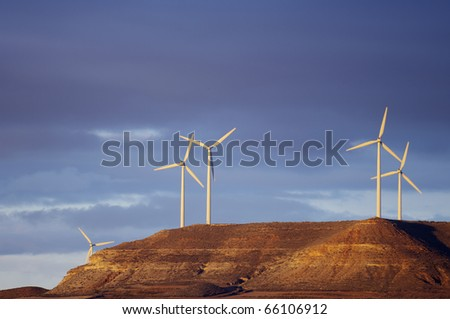 sunrise view of a group of windmills on a hill - stock photo