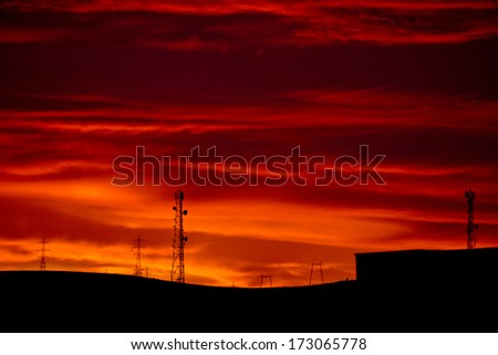 Sunrise view towards a hill covered by an electricity network