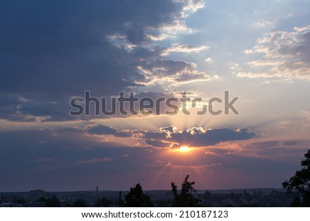sunrise with a dense fog and dramatic sky with the silhouette of the city in the foreground