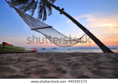 Sunrise with coconut palm trees and hammock on tropical beach background, happy summer holiday concept