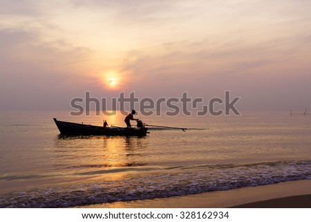 Sunrise with fisherman and boat  Songkhla Lake,Songkhla Thailand.Shallow depth of field, focus at fisherman boat.