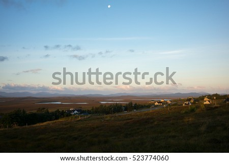 Sunrise with moon in the sky on the isle of Lewis with hills in the background