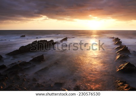 Sunrise with stormy clouds on the rocky coast The rock strata is from the Cretaceous period and the area is designated as natural monument. - stock photo