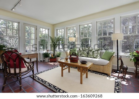 Sunroom in suburban home with red brick flooring - stock photo