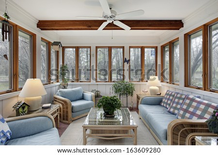 Sunroom with wood ceiling beam and wicker furniture - stock photo