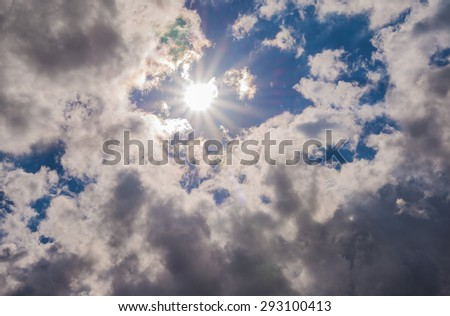 Suns rays beaming from behind clouds