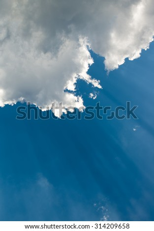 Suns rays beaming from behind clouds in sky - stock photo