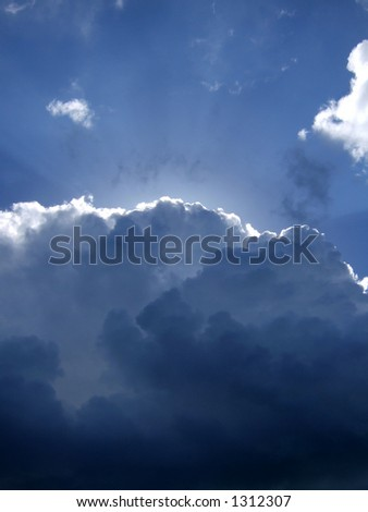 Suns rays burst out from behind a dark cloud - stock photo